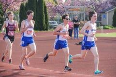 Männliche Highschool Athleten gruppieren sich nahe Anfang des 3000-Meter-Rennens Stockbilder