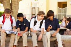 Männliche hohe Schüler, die Handys auf Schulcampus verwenden Stockfotos