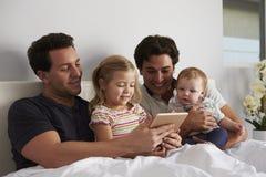 Männliche homosexuelle Eltern, die Tablet-Computer im Bett mit zwei Kindern verwenden lizenzfreies stockfoto
