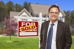 Männliche Immobilienagentur vor Verkaufszeichen und Haus Stockbilder