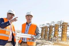 Männliche Ingenieure, die an der Baustelle gegen klaren Himmel sich besprechen Stockfotos