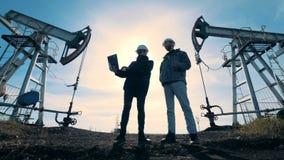 Männliche Ingenieure sprechen bei der Stellung zwischen pumpenden Maschinen des Brennstoffs Energie, Öl, Gas, pumpende Anlage des