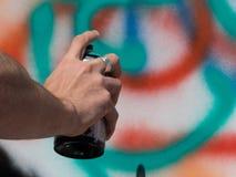 Männliche Künstlerhand, die Farbenspraynahaufnahme hält Stockbild