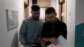 Männliche Kollegen besprechen die Arbeitsfragen, die im Korridor des Bürogebäudes gehen stock footage