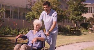 Männliche Krankenschwester, die ältere Frau auf Rollstuhl im Hinterhof unterstützt stock video footage