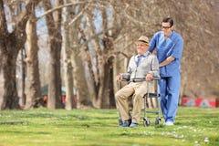 Männliche Krankenschwester, die draußen einen Senior im Rollstuhl drückt Stockfoto