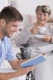 Männliche Krankenschwester, die ein Buch zum Senior liest lizenzfreie stockfotografie
