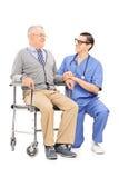 Männliche Krankenschwester, die mit einem älteren Patienten spricht Stockfoto