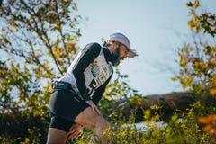 Männliche Läuferabschlussklassenahaufnahme, die oben einen Hügel laufen lässt Stockfotografie