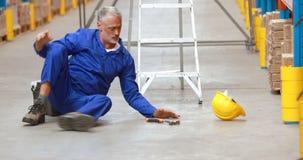 Männliche Lagerarbeitskraft, die weg Leiter beim Arbeiten fällt stock footage