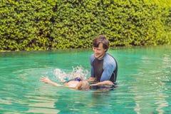 Männliche Lehrerschwimmen für Kinder unterrichtet einen glücklichen Jungen, im Pool zu schwimmen lizenzfreies stockbild