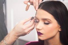 Männliche Make-upkünstler Colors-Augenbrauen zum Brunettemädchen in einem beaty Salon, Abschluss oben Lizenzfreie Stockfotos