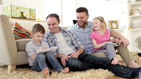 Männliche Paare, die ihren Kindern mit Hausarbeit helfen stock video footage