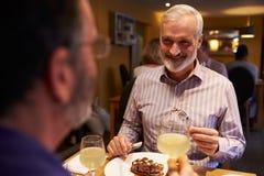 Männliche Paare, die Mahlzeit in einem Restaurant, Überschulteransicht essen Lizenzfreies Stockbild