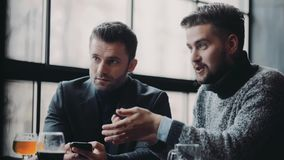 Männliche Partei, drei junge attraktive Freunde in der Freizeitkleidung haben ein Gespräch, die Männer in den Shows eines Anzugs  stock video footage