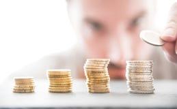 Männliche Person, die oben Stapel der Euromünzen anhäuft lizenzfreie stockfotografie