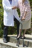 Männliche Pflegekraft, die einem älteren pation mit Spazierstock hilft Lizenzfreie Stockbilder