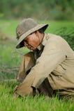 Männliche Reisarbeitskraft duckt sich, während er am neuen Reis zerrt, um ihn vorzubereiten f Stockbilder