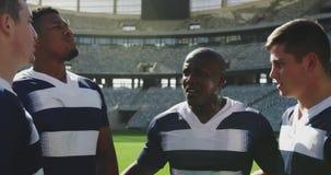 Männliche Rugbyspieler, die zusammen im Stadion 4k stehen stock footage