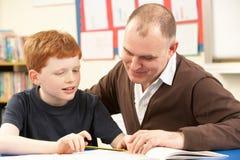 Männliche Schüler, die im Klassenzimmer mit Lehrer studiert Lizenzfreie Stockfotos