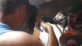 Männliche Schlosser- oder Mechanikerarbeitskraftschweißungen asphaltieren Teile des alten Autos mit Schweißgerät in der Garage Er stock footage