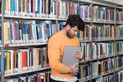 Männliche Student-Stressed About His-Hausarbeit stockfotografie