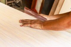 Männliche Tischlerhände, welche manuell die Tischkante, zuhause versanden lizenzfreie stockfotografie