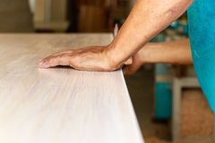 Männliche Tischlerhände, welche manuell die Tischkante, zuhause versanden lizenzfreies stockfoto