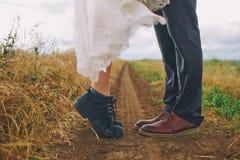 Männliche und weibliche Beine in den Stiefeln auf dem Gebiet Liebe, Kusskonzept stockfotos