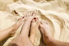 Männliche und weibliche Beine entwirrten sich im Sand auf dem Strand Stockfoto
