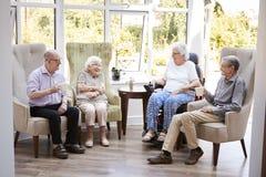Männliche und weibliche Bewohner, die in den Stühlen sitzen und im Aufenthaltsraum des Ruhesitzes sprechen lizenzfreies stockfoto