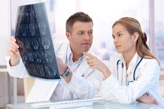Männliche und weibliche Doktoren, die im Büro sich beraten lizenzfreie stockfotos