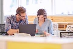 Männliche und weibliche Geschäftsfachleute, die im Büro zusammenarbeiten Lizenzfreies Stockbild