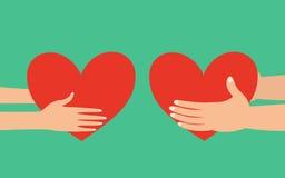Männliche und weibliche Hände, die Herz geben Stockfotos