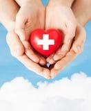 Männliche und weibliche Hände mit rotem Herzen lizenzfreies stockfoto