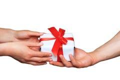 Männliche und weibliche Hände mit weißer Geschenkbox mit Bogen über Weiß Stockfotos