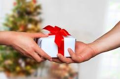 Männliche und weibliche Hände mit weißer Geschenkbox mit einem Bogen Stockbilder