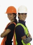 Männliche und weibliche Hardhatarbeitskräfte stockfoto