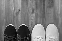 Männliche und weibliche Schuhe auf hölzernem Hintergrund stockfotografie