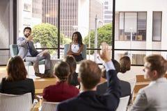 Männliche und weibliche Seminarsprecher bringen Frage vom Publikum vor stockfotografie