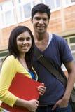 Männliche und weibliche Studenten auf Campus Stockfotos