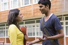 Männliche und weibliche Studenten, die auf Campus sprechen Stockfoto