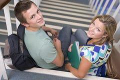 Männliche und weibliche Studenten, die auf Treppen sitzen Stockbild