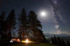 Männliche Wanderer enjoyng Nacht, die nahe touristischem Zelt am Lagerfeuer unter blauem sternenklarem Himmel und Milchstraße kam stockfoto