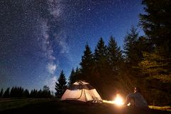 Männliche Wanderer enjoyng Nacht, die nahe touristischem Zelt am Lagerfeuer unter blauem sternenklarem Himmel und Milchstraße kam stockbild