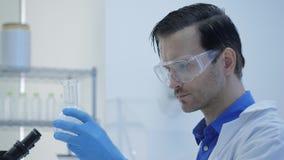 Männliche Wissenschaftler der medizinischen Forschung setzten Trockeneis in einen Glasbecher stock video