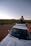 Männlicher überwachender Sonnenuntergang vom Dach des Autos Stockfotografie