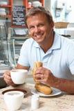 Männlicher Abnehmer, der Sandwich und Kaffee im Kaffee genießt Lizenzfreie Stockfotografie
