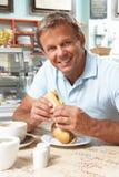 Männlicher Abnehmer, der Sandwich und Kaffee im Kaffee genießt Stockfotos