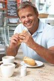 Männlicher Abnehmer, der Sandwich und Kaffee im Kaffee genießt Stockbild